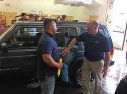 Auburn Career Center auto collision repair instructor Justin Bruno discusses using clay bar treatment to enhance vehicle finish with Superintendent Brian Bontempo.
