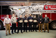 A group of firefighters standing in front of a fire truck with masks and certificates