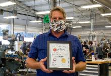 teacher in a mask holding a certificate