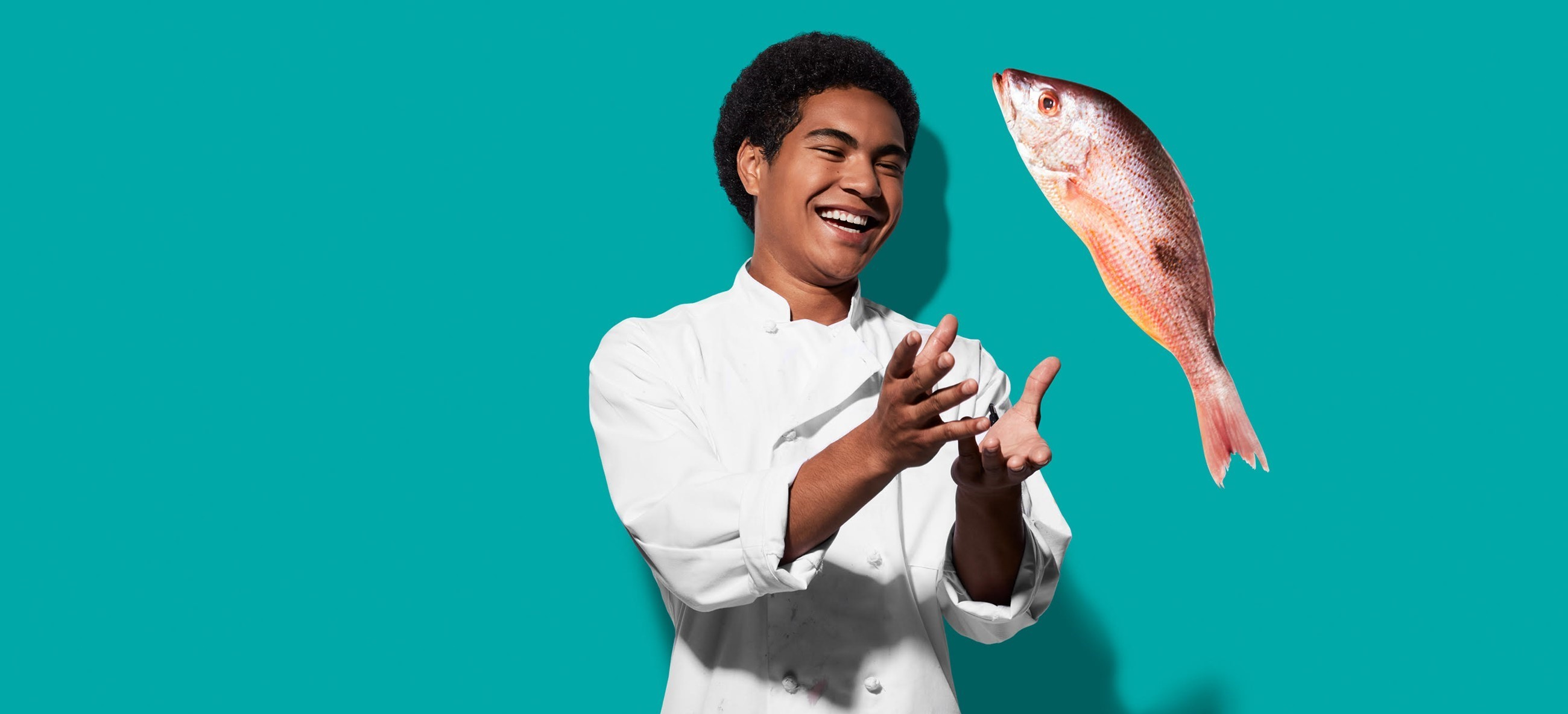 Student in chef coat with fish