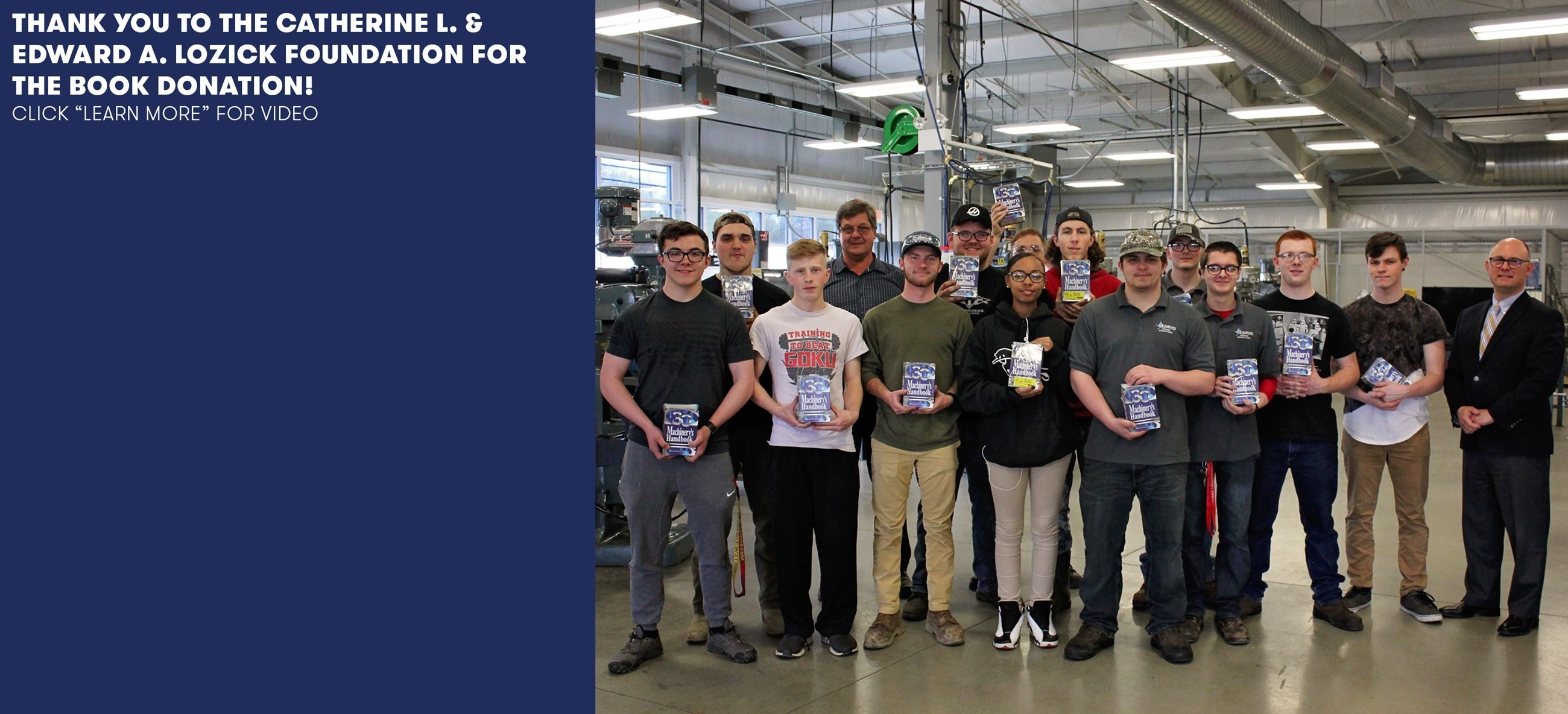 students holding books in a manufacturing classroom