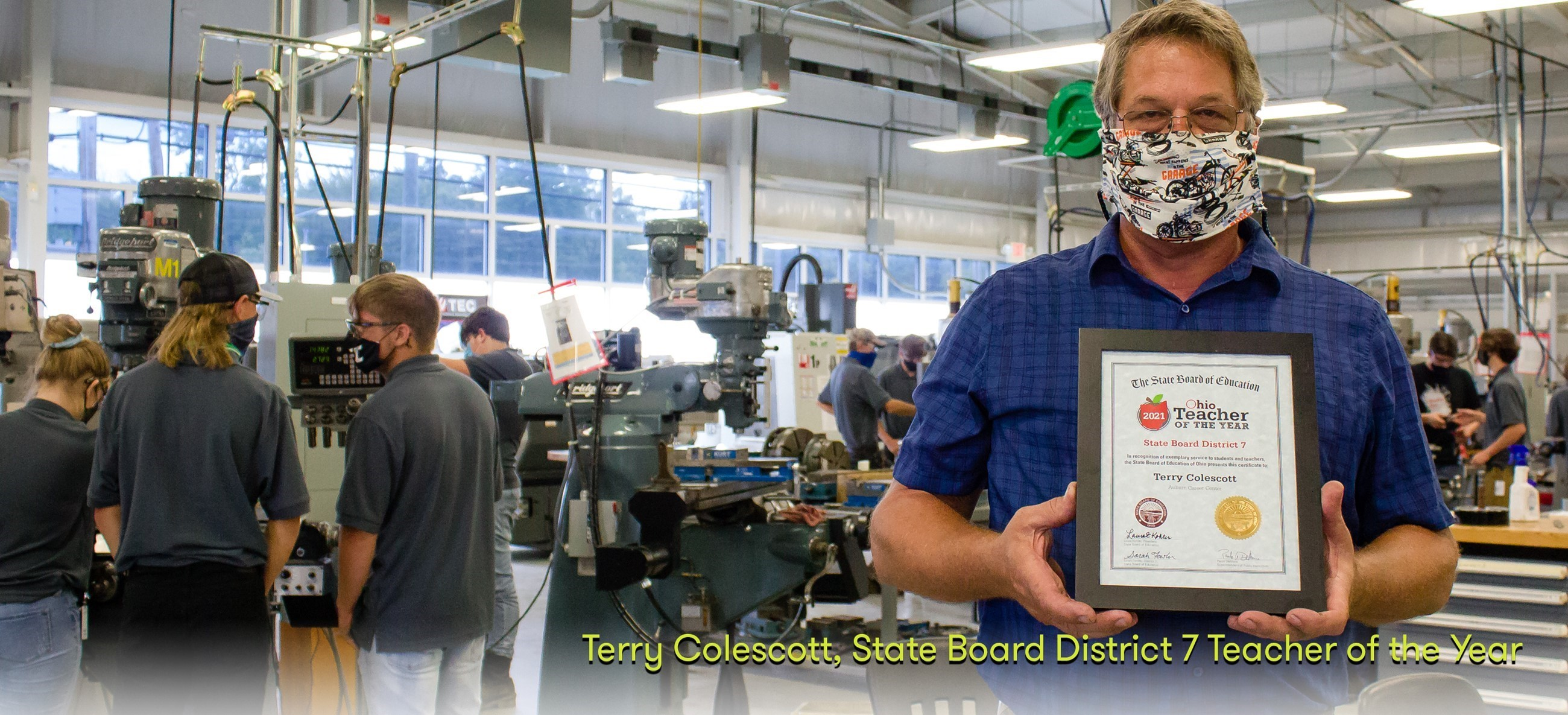 teacher in a mask holding certificate in manufacturing lab