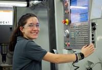 female student smiling working on cnc machine