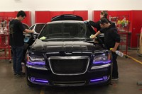 students working on a car with lights