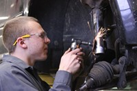 student working on a vehicle on a lift and grinding by the wheel well
