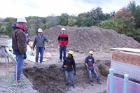 students working with instructor building a house