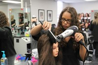 student blow drying and styling a mannequin's hair