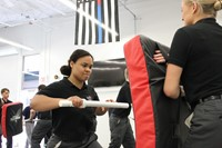 female student striking a pad held by another student