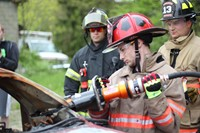 student in protective fire safety gear working on cutting a vehicle