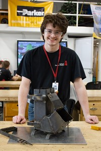 smiling student standing proudly by a rocket stove he made