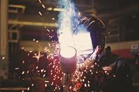 welder with helmet welding with sparks flying