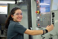 female student smiling working on cnc machine