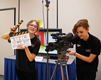 Two female students - one looking through a video camera and one with a sign